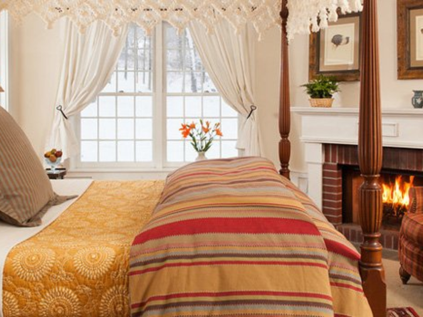 A bedroom with a bed and a fireplace at The Garden Gables Inn.