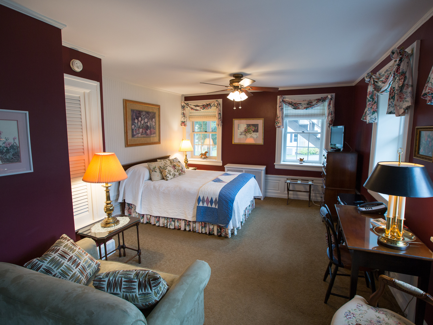 A living room filled with furniture and a large window at Genesee Country Inn Bed and Breakfast.