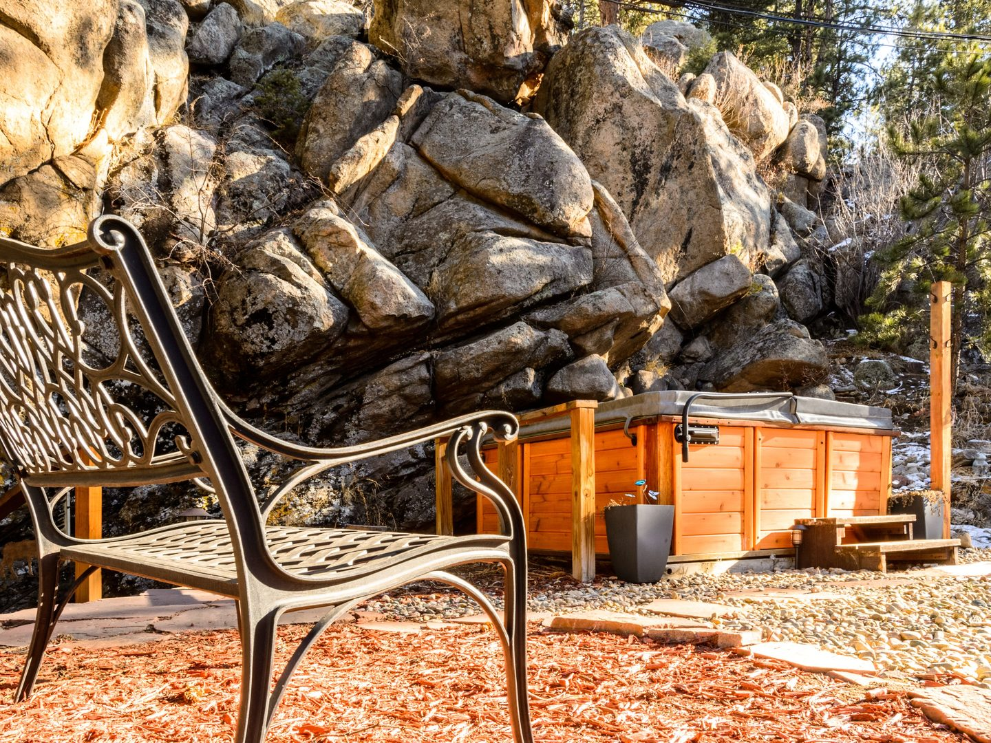 A chair sitting in front of a large rock at Alpen Way Chalet Mountain Lodge.