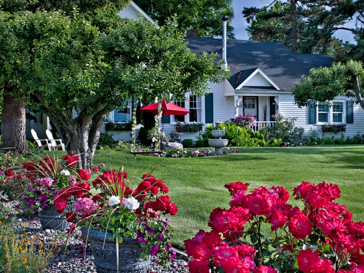 A close up of a flower garden in front of a house at Cozy Rose Bed and Breakfast.