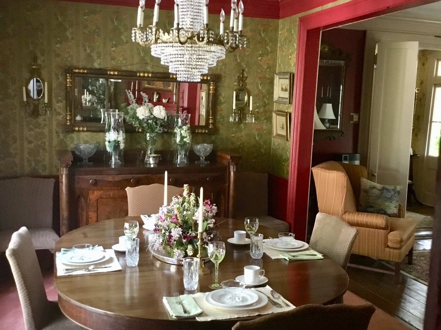 A dining room filled with furniture and vase of flowers on a table at The Governor's Bed and Breakfast.