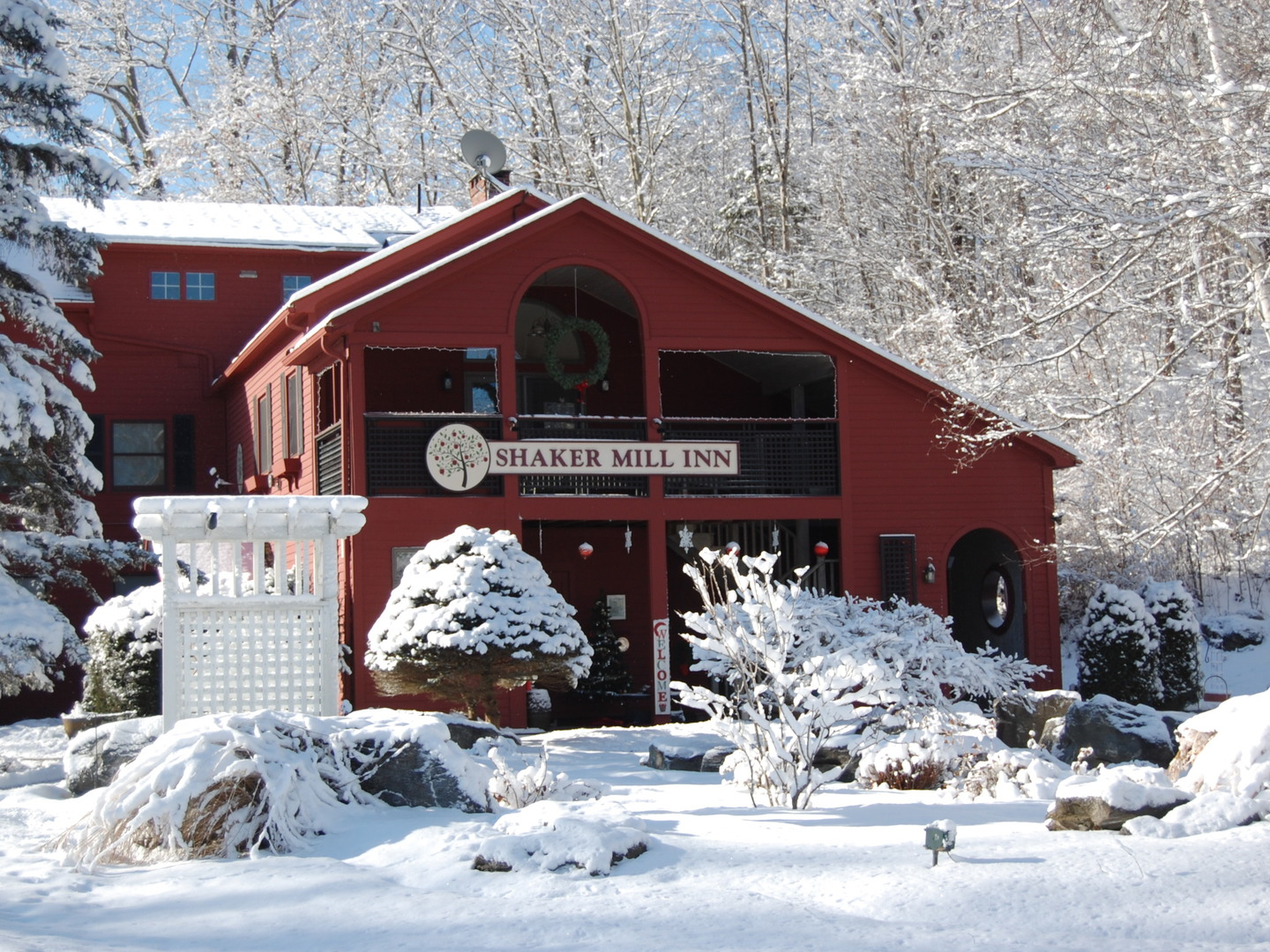 A house covered in snow with covered bridge in the background at Shaker Mill Inn.