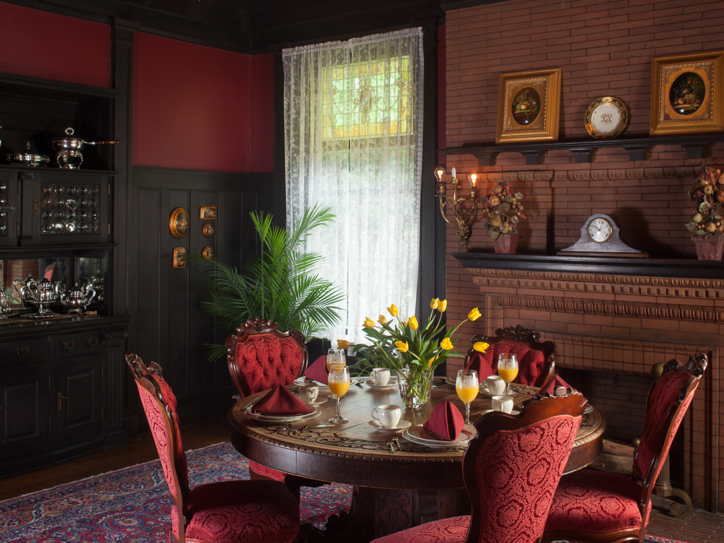 A living room filled with furniture and vase of flowers on a table at Vrooman Mansion.