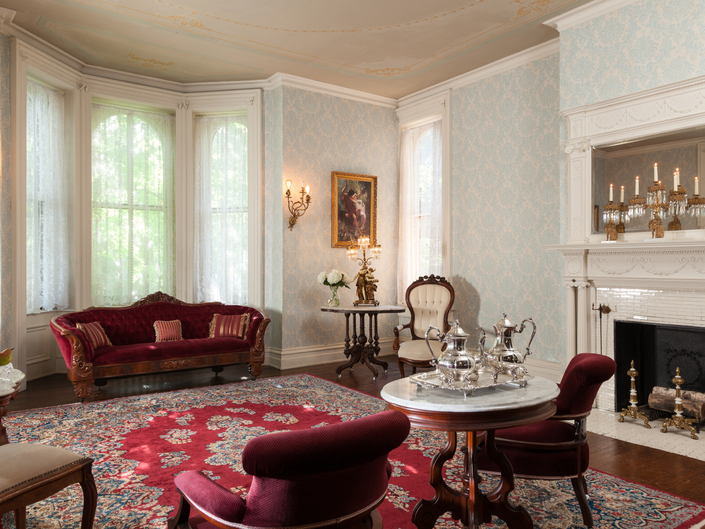A living room filled with furniture and a fire place at Vrooman Mansion.