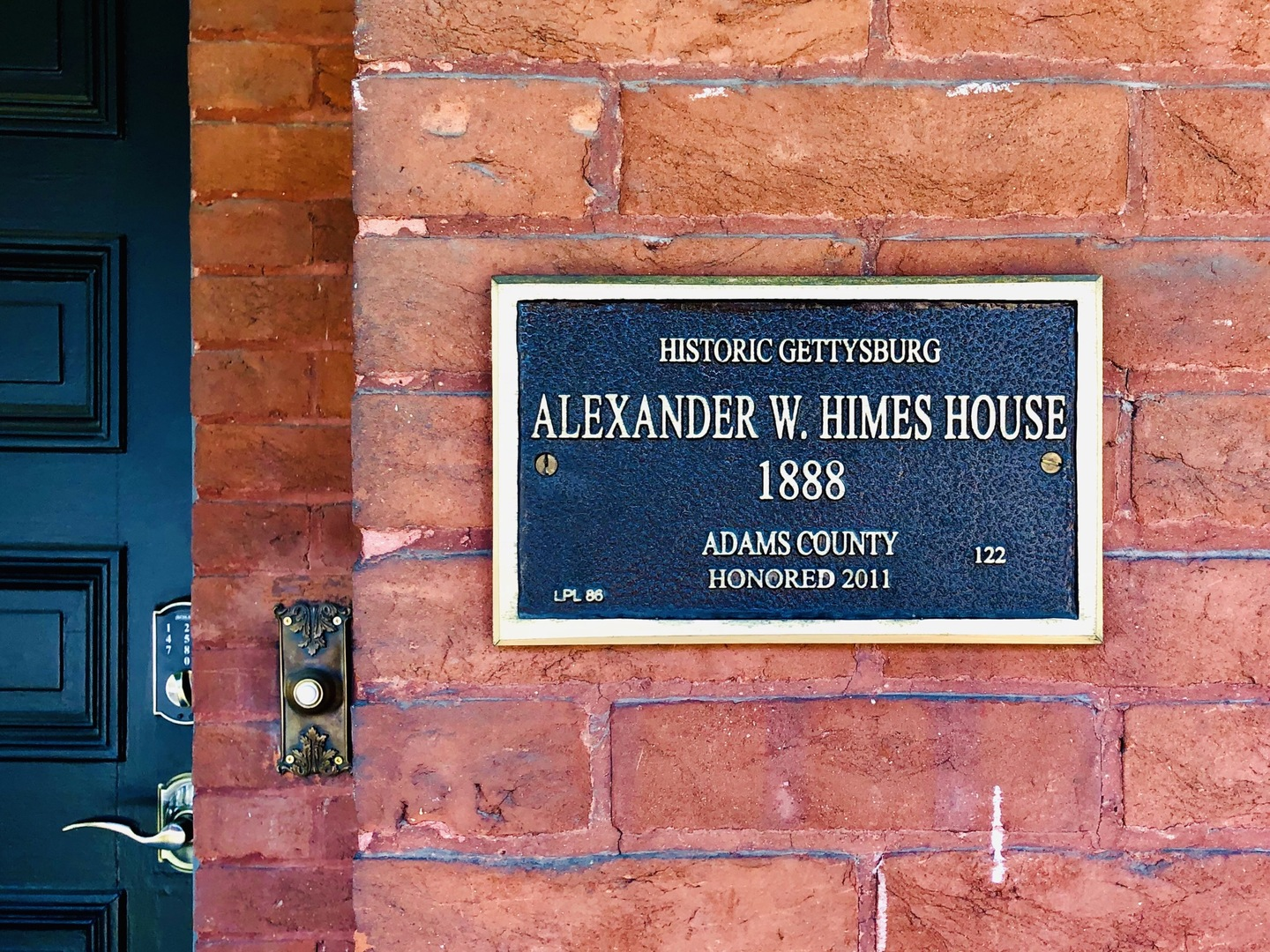 A sign on the side of a brick wall at Himes House Bed & Breakfast.
