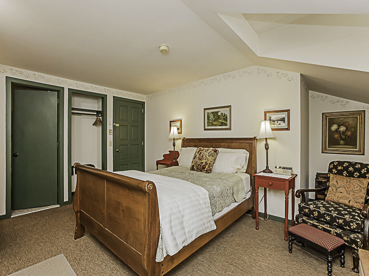 A bedroom with a bed and a chair in a room at Captain Stannard House Bed and Breakfast Country Inn.
