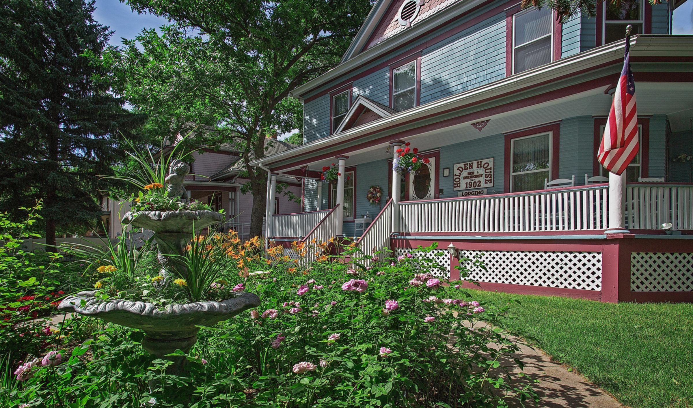 A colorful flower garden in front of a building at Holden House 1902 Bed & Breakfast Inn.