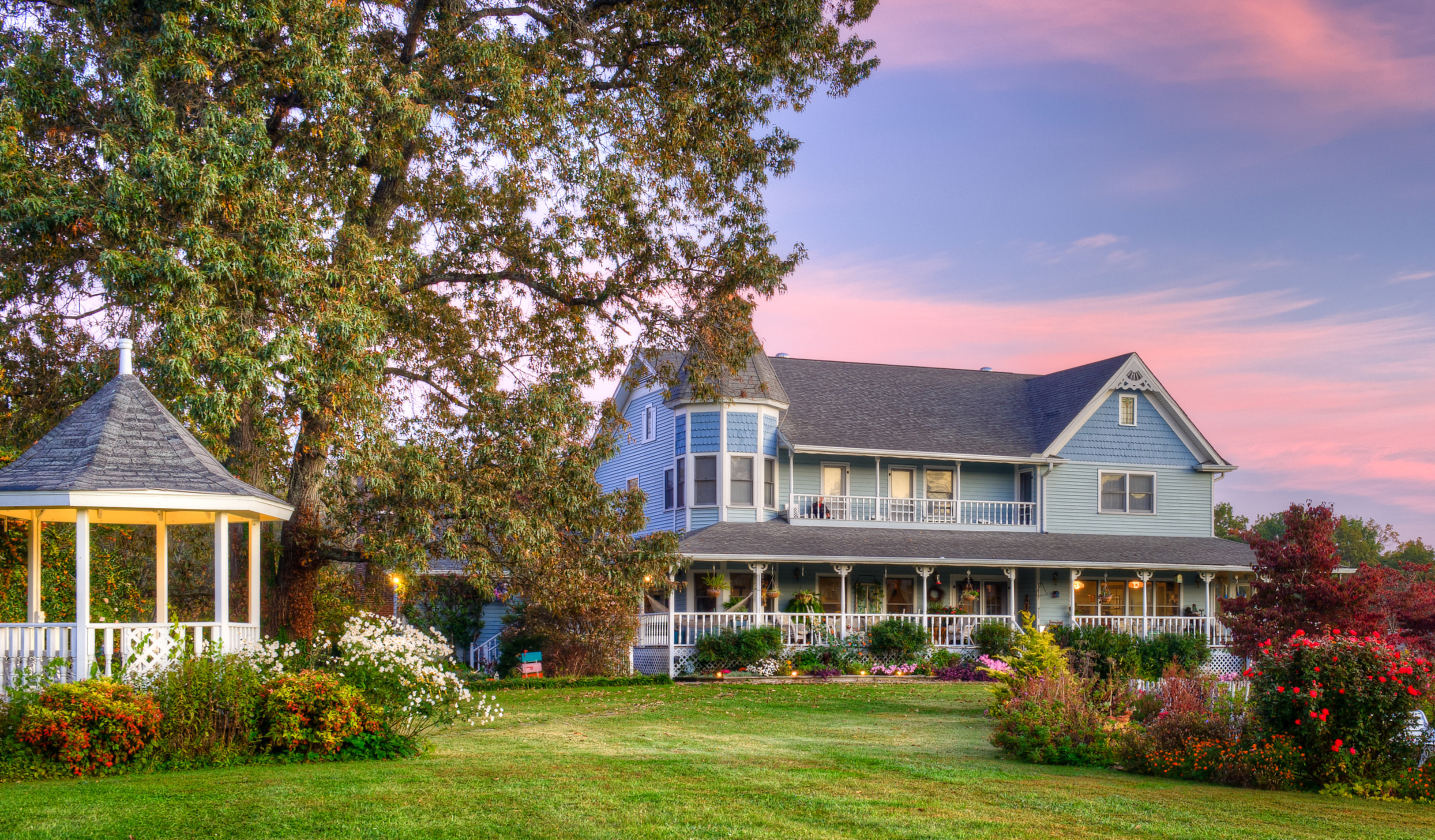 A house with bushes in front of a building at Blue Mountain Mist Country Inn and Spa.
