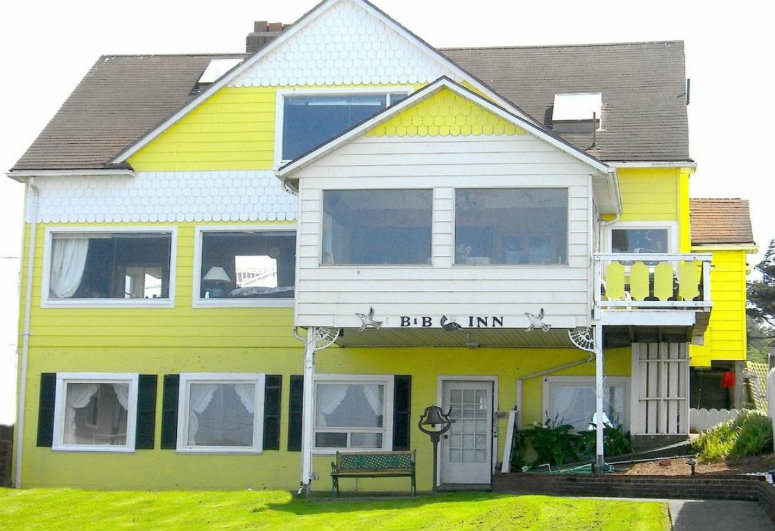 A yellow house in the background at Brey House Ocean View Bed and Breakfast.