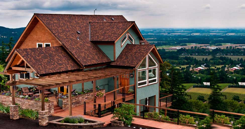 A large brick building with a mountain in the background at Chehalem Ridge Bed and Breakfast.