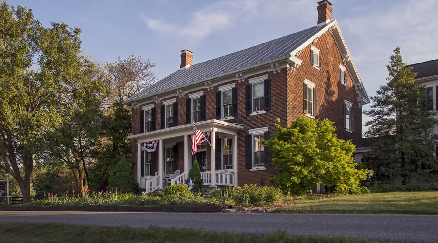 A large brick building with grass in front of a house at Pheasant Field Bed and Breakfast.