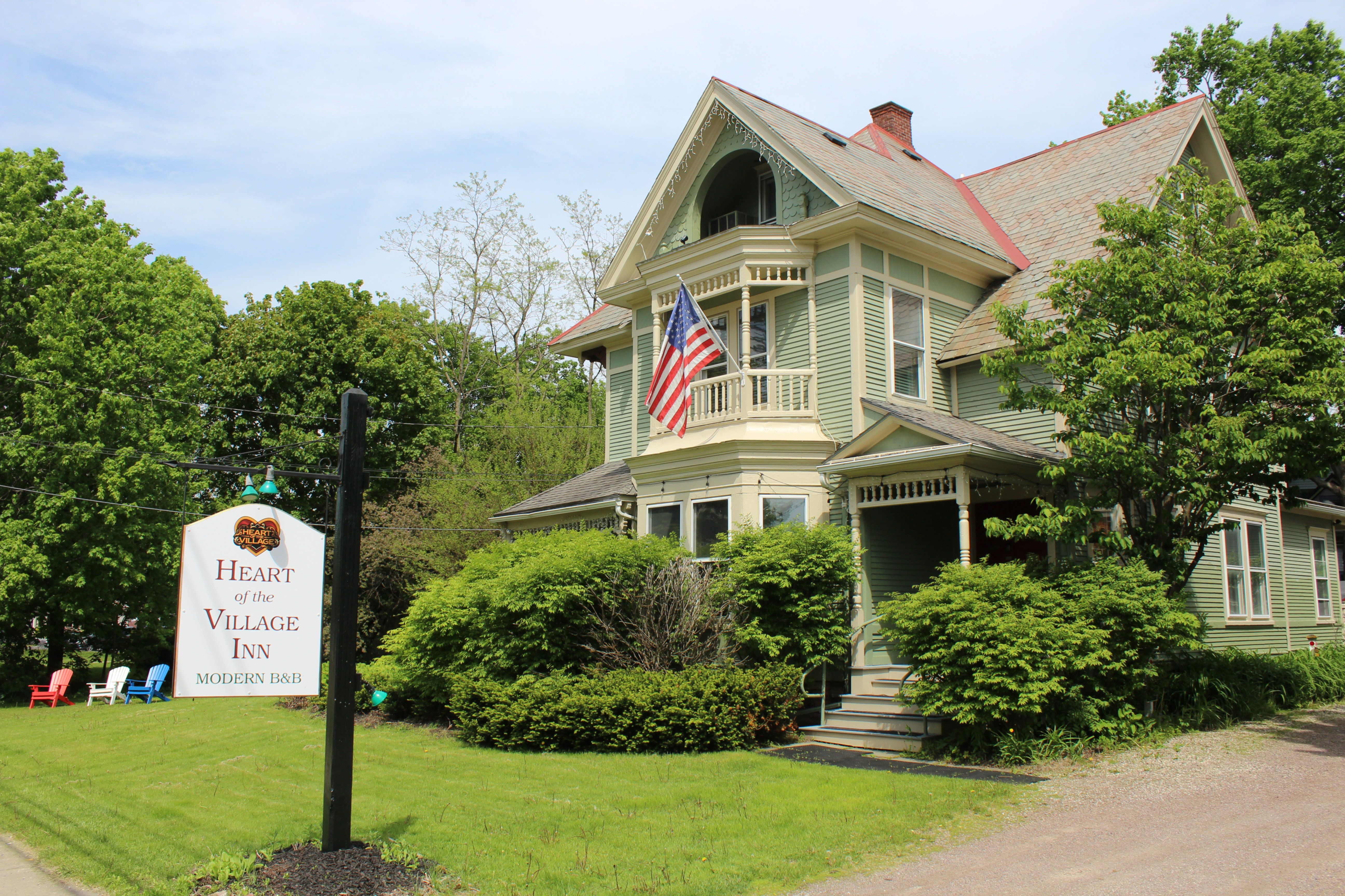 A large lawn in front of a house at Heart of the Village Inn, Modern Vermont Bed & Breakfast.