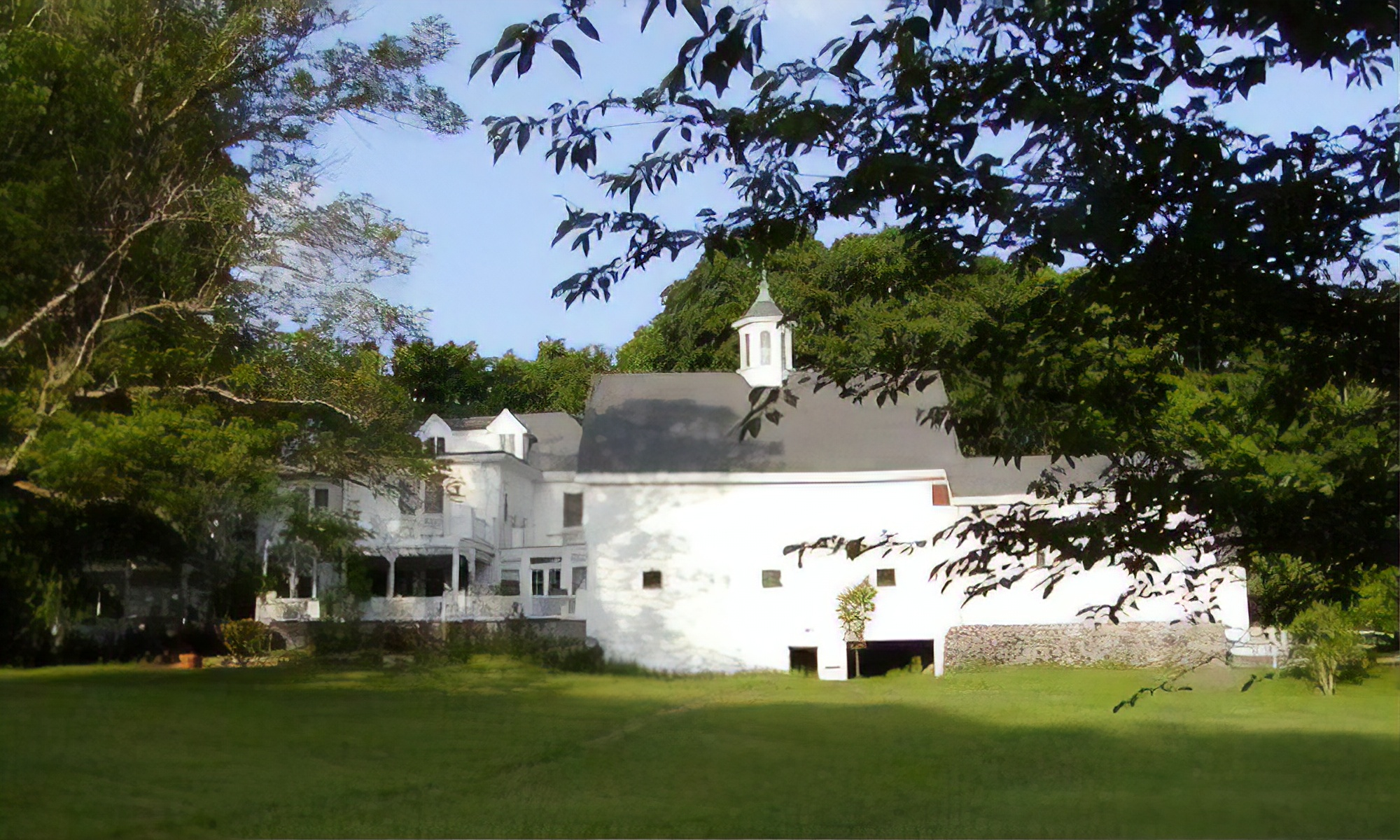 A large white building with a grassy field with trees in the background at Inn On The Horse Farm.