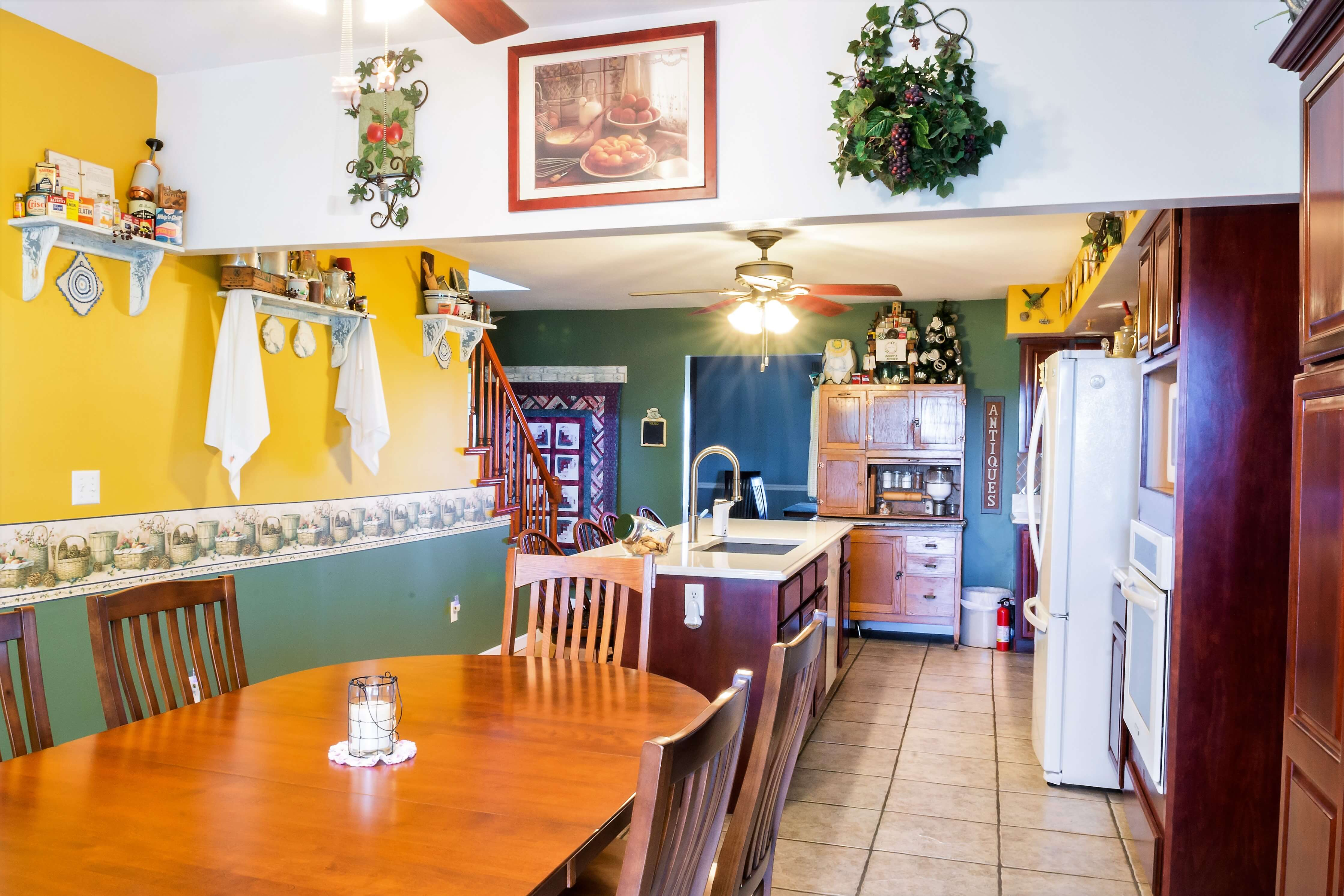 A kitchen with wooden cabinets and a dining room table at Timmermann House Bed & Breakfast.