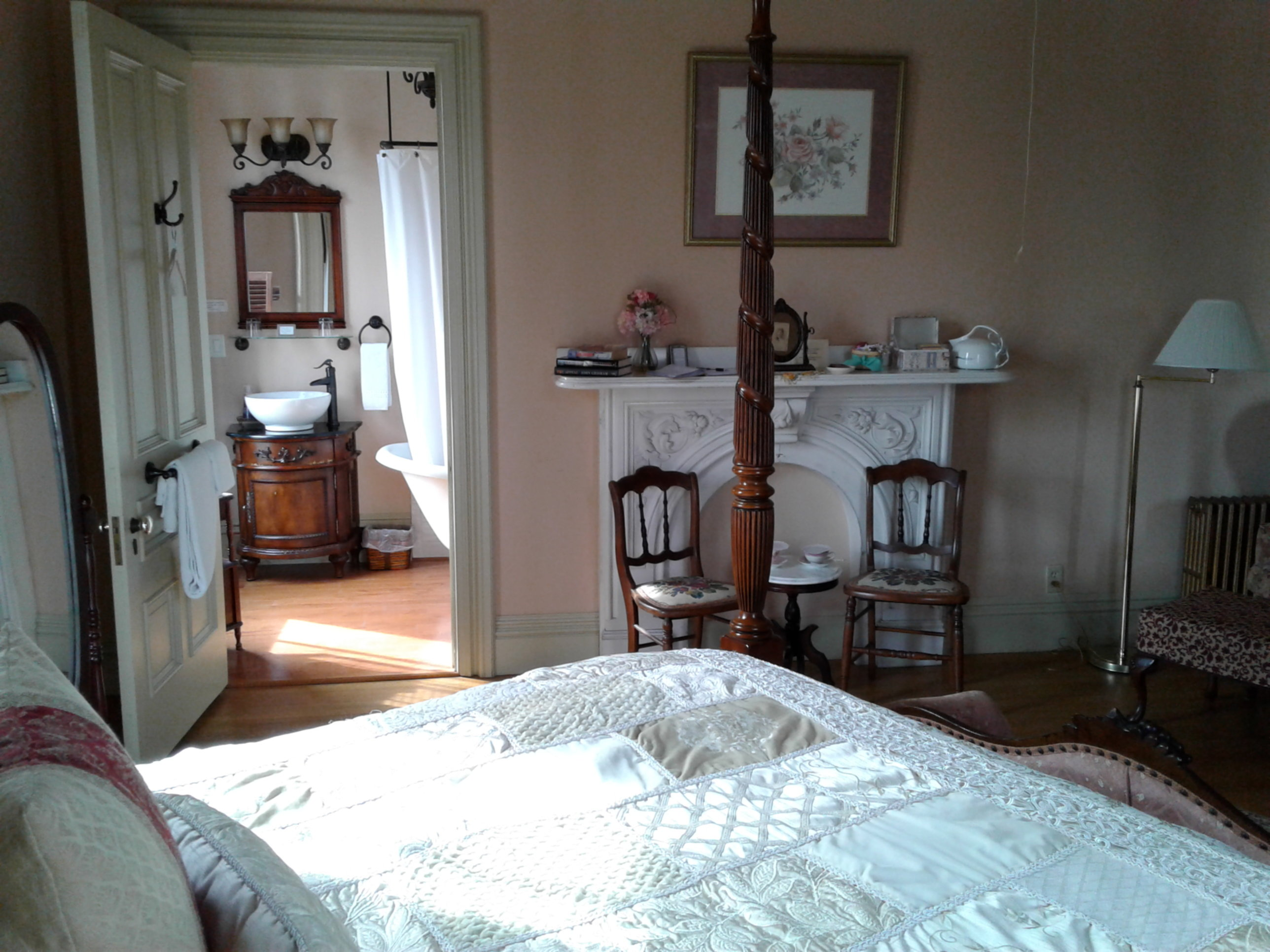 A bedroom with a bed and a chair in a room at Proctor Mansion Inn.