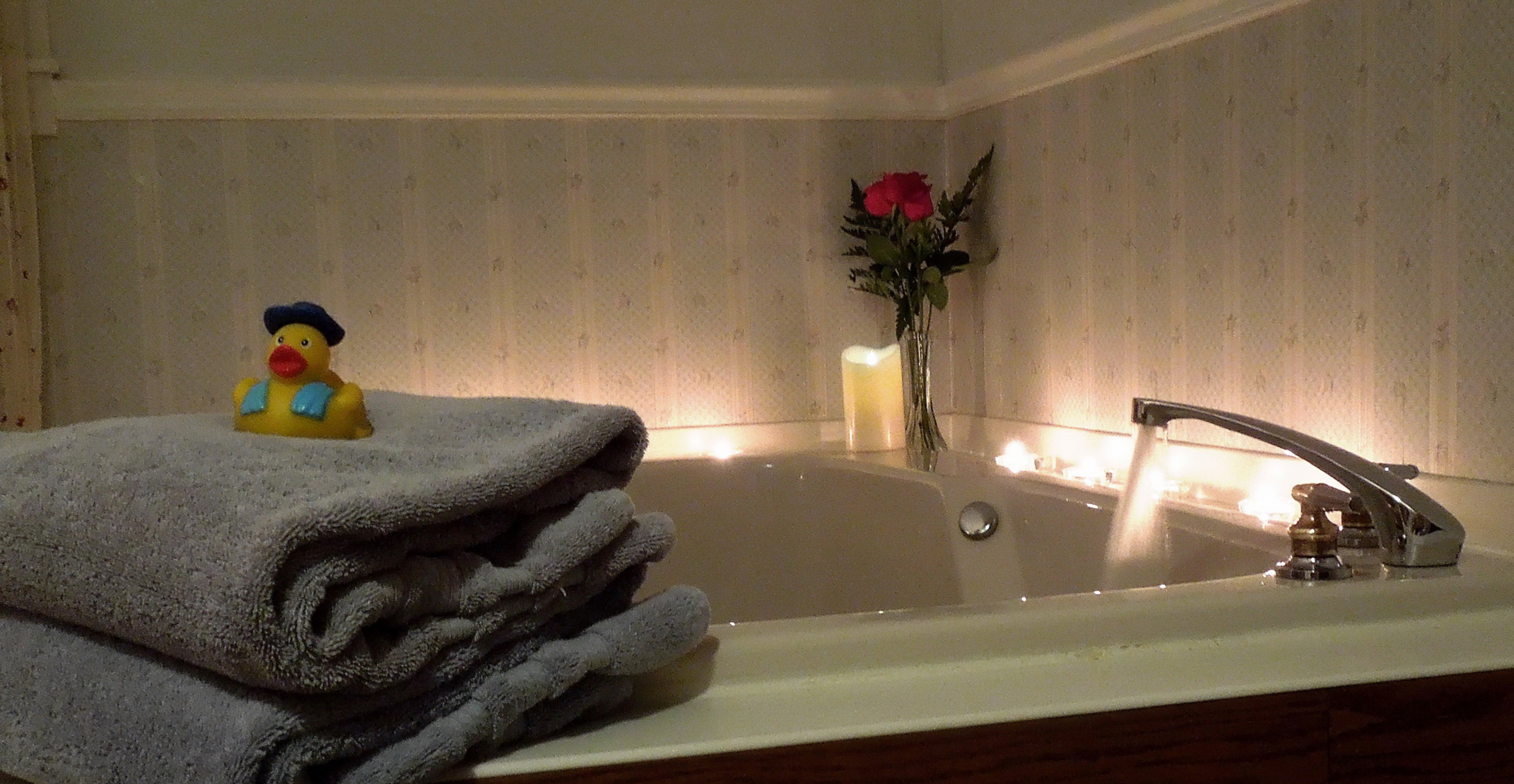 A white tub sitting next to a sink at Candlelite Inn Bed & Breakfast.