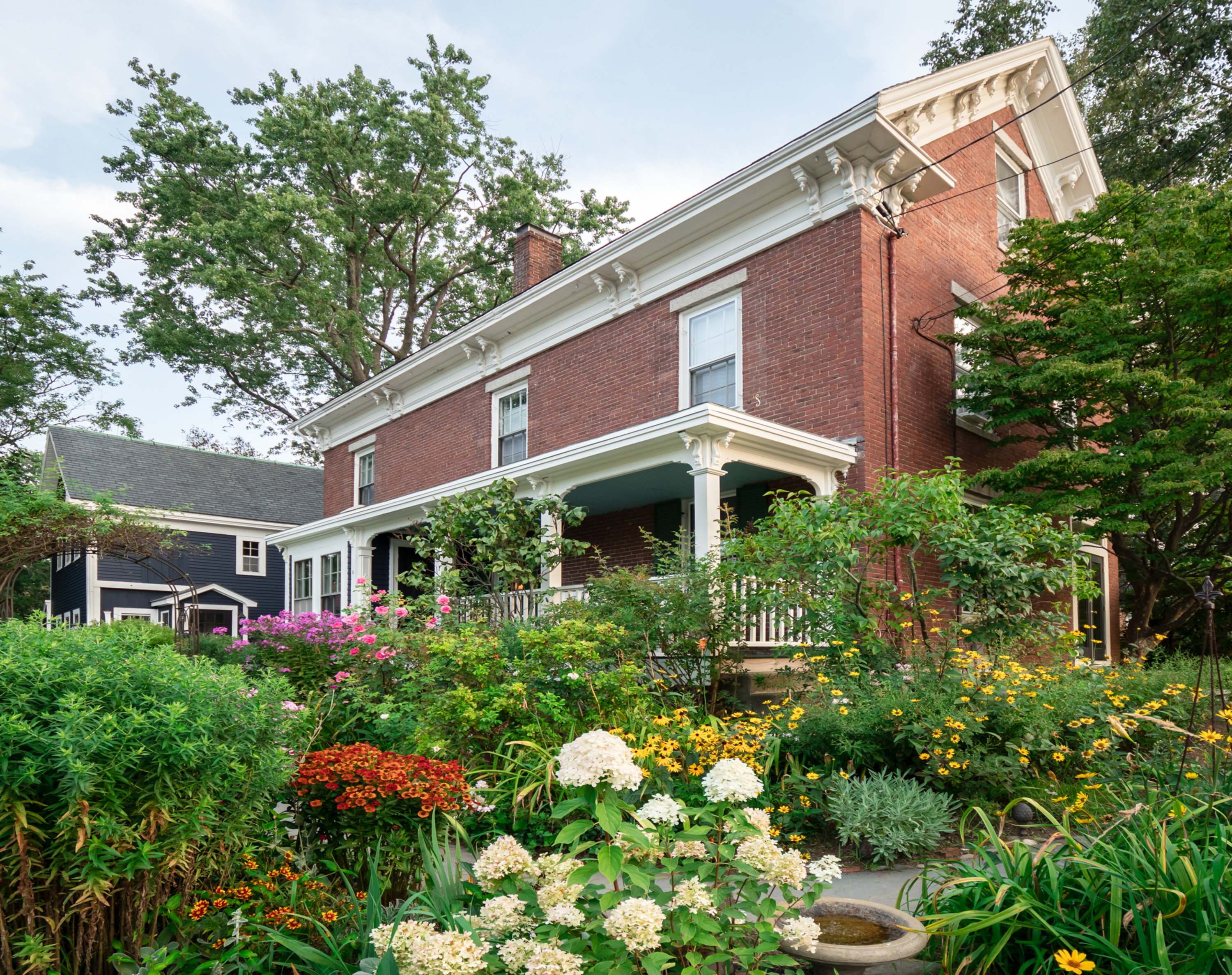 A house with bushes in front of a brick building at Water Street Inn.