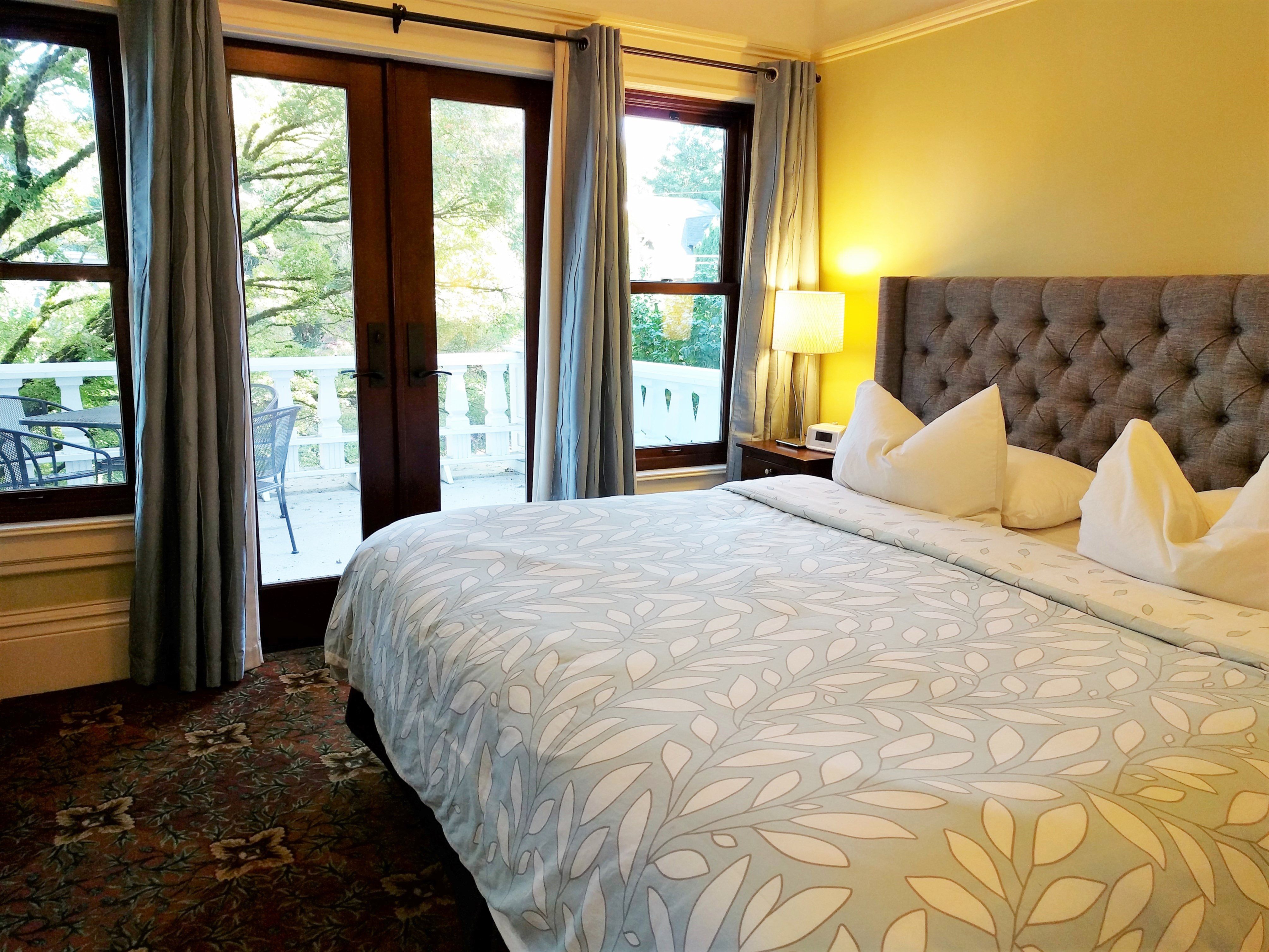 A bedroom with a large bed sitting next to a window at Evermore Guesthouse - Division Inns.