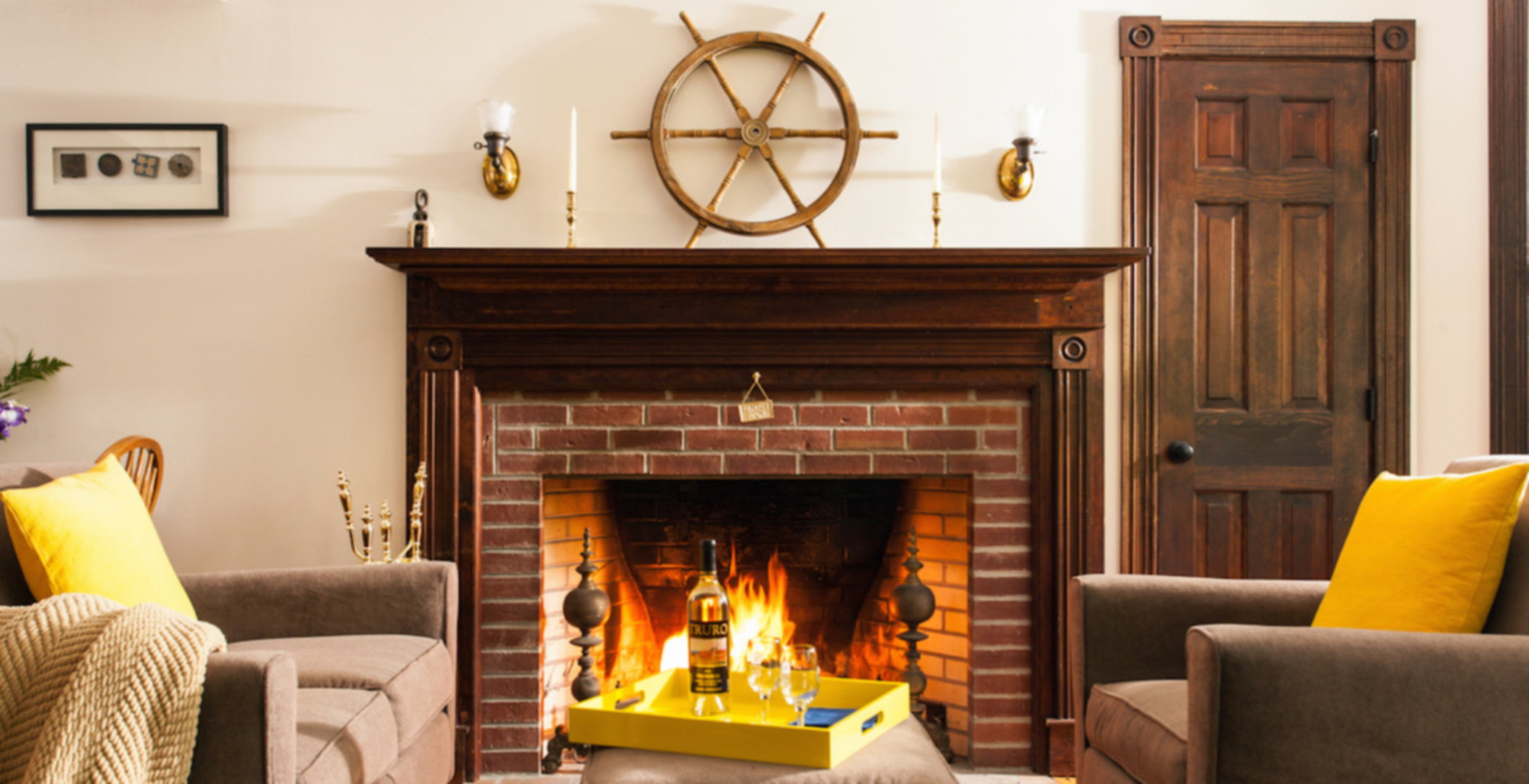 A fireplace in a living room filled with furniture and a fire place at The Inn at the Oaks .