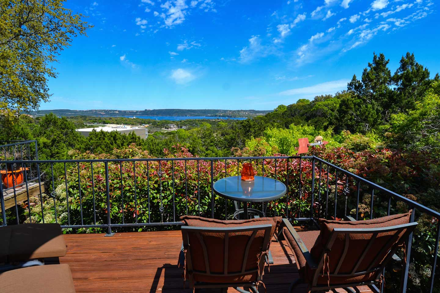 A chair sitting in front of a forest at Casa Del Sol Bed and Breakfast at Lake Travis.