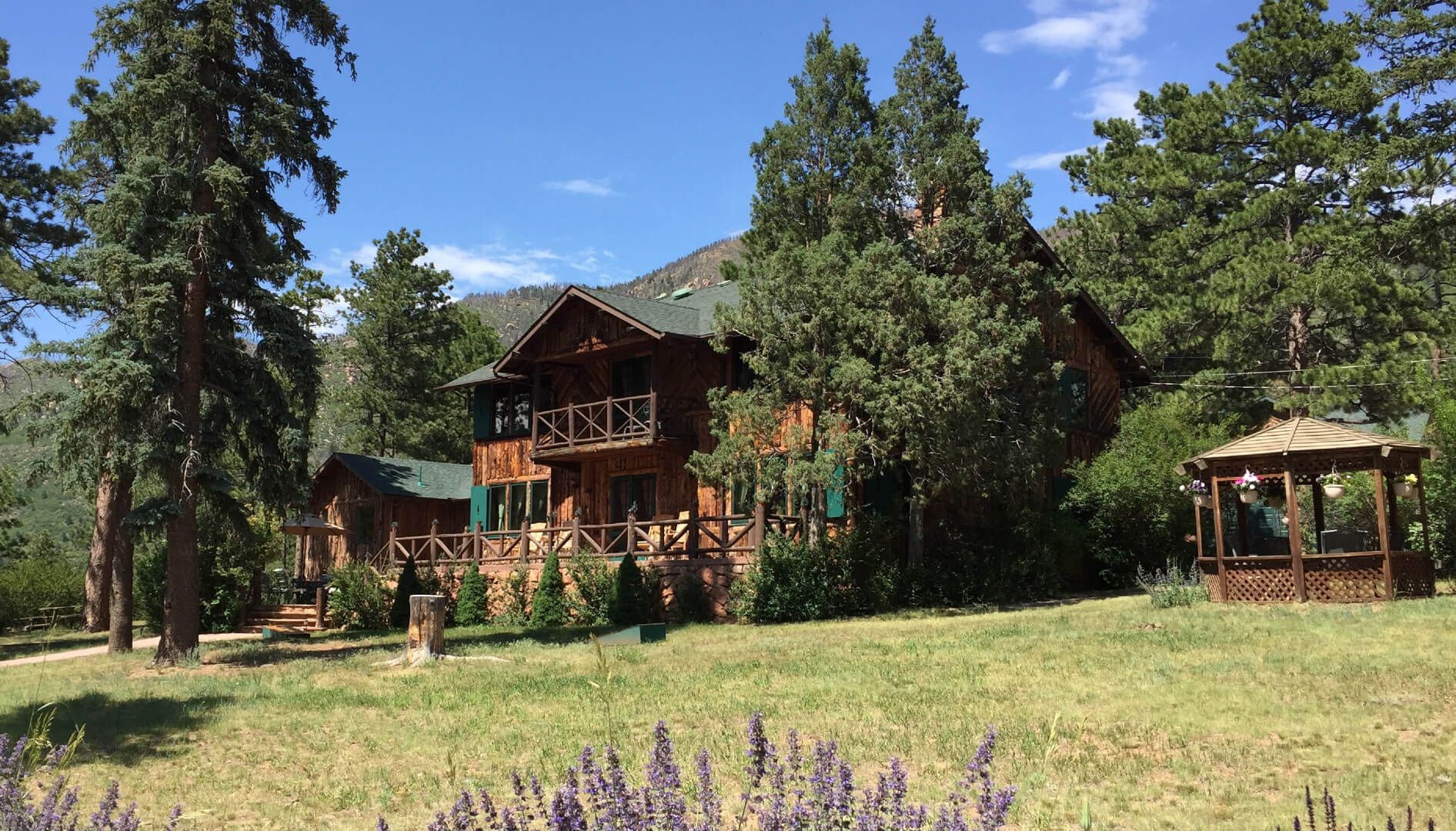 A house with a grass field at Rocky Mountain Lodge.
