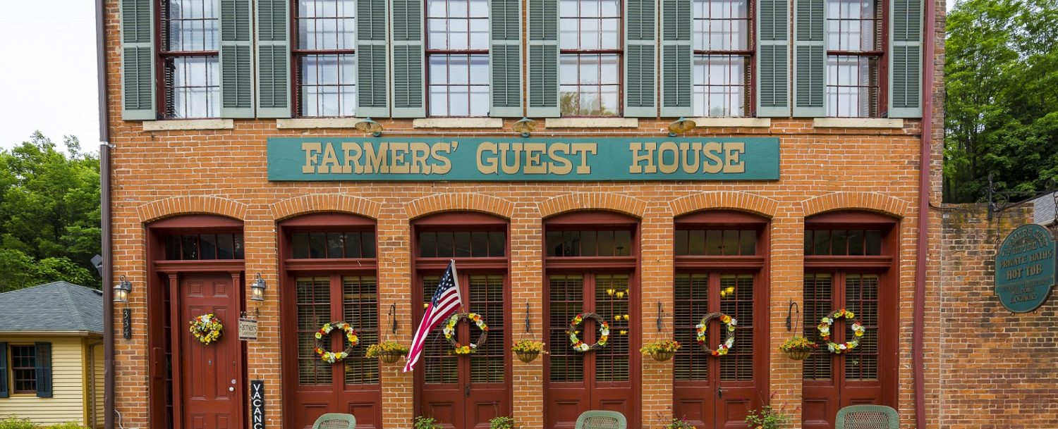 A sign in front of a brick building at Farmer's Guest House.