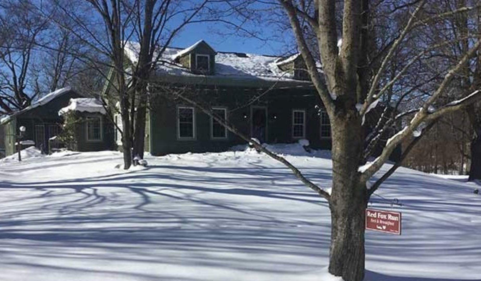 A house covered in snow at Red Fox Run Bed & Breakfast.