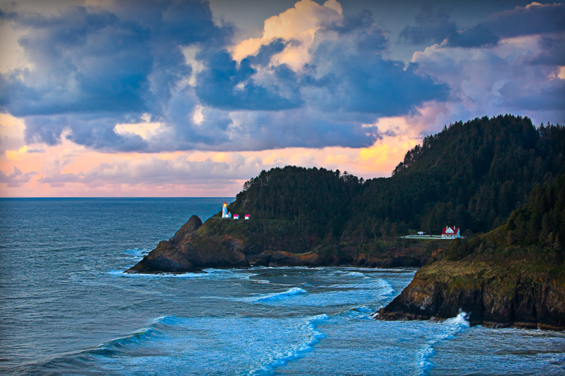 A body of water with a mountain in the background at Heceta Lighthouse B&B.