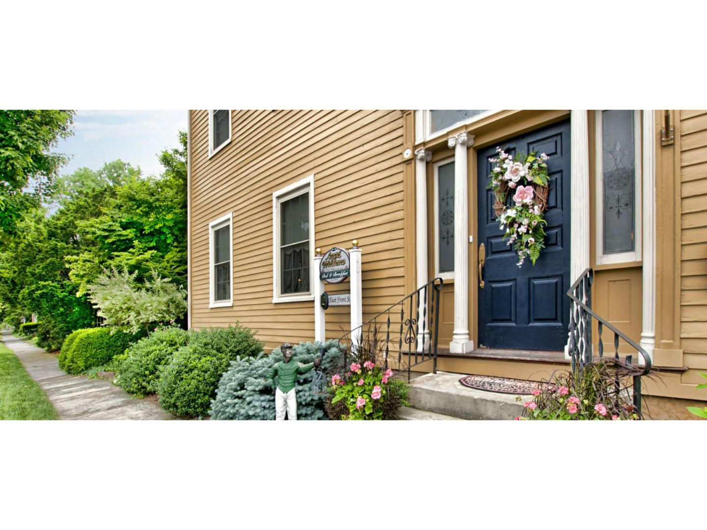 A house with bushes in front of a brick building at Angel Welcome - A Charming Bed & Breakfast.