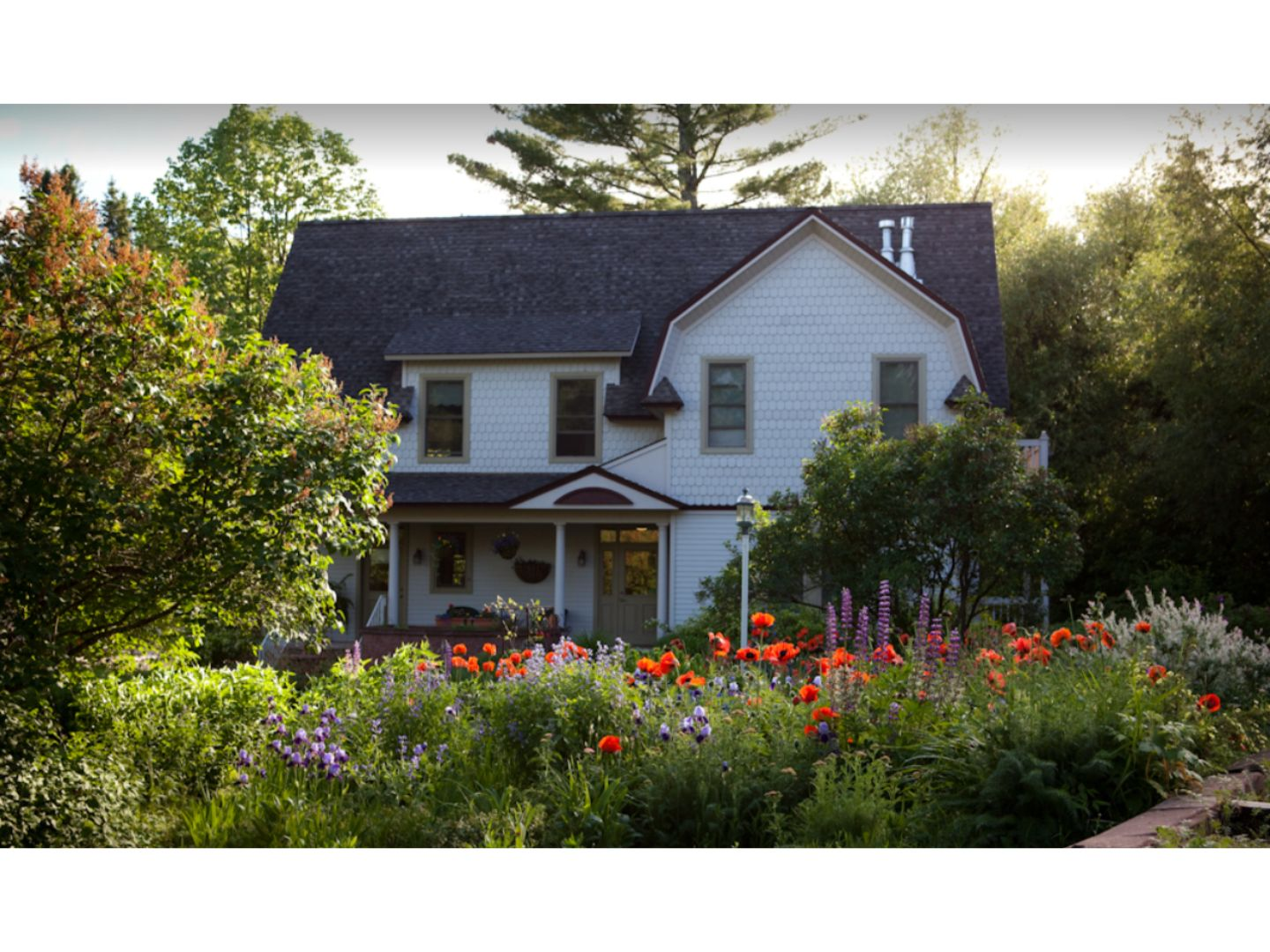 A close up of a flower garden in front of a house at Pinehurst Inn Bed & Breakfast.