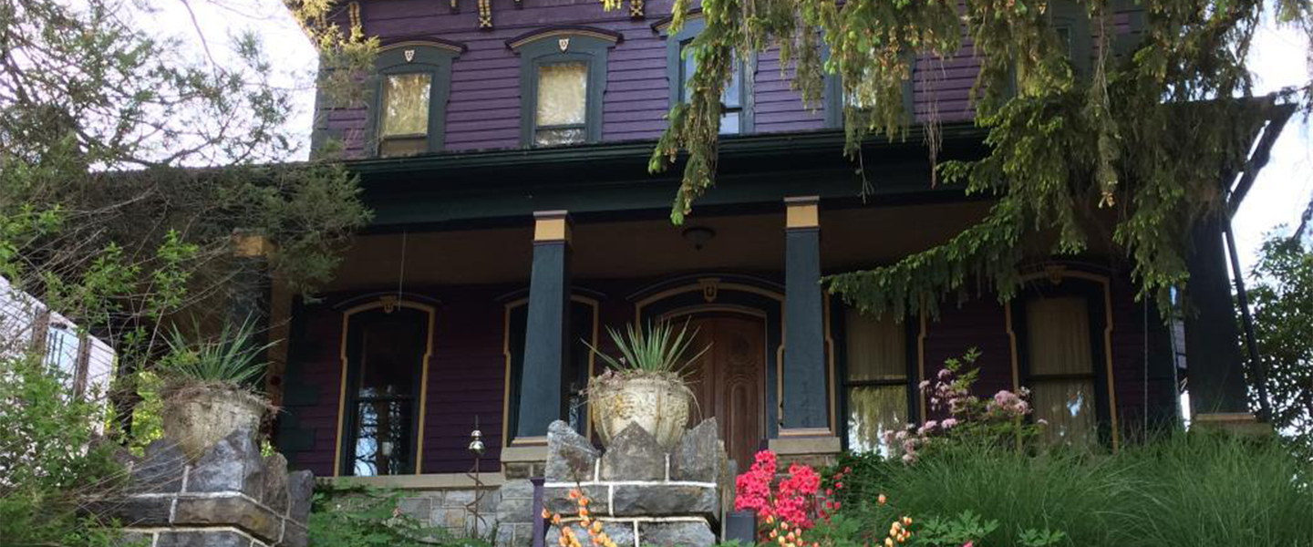 A vase of flowers sits in front of a house at Amethyst Inn.