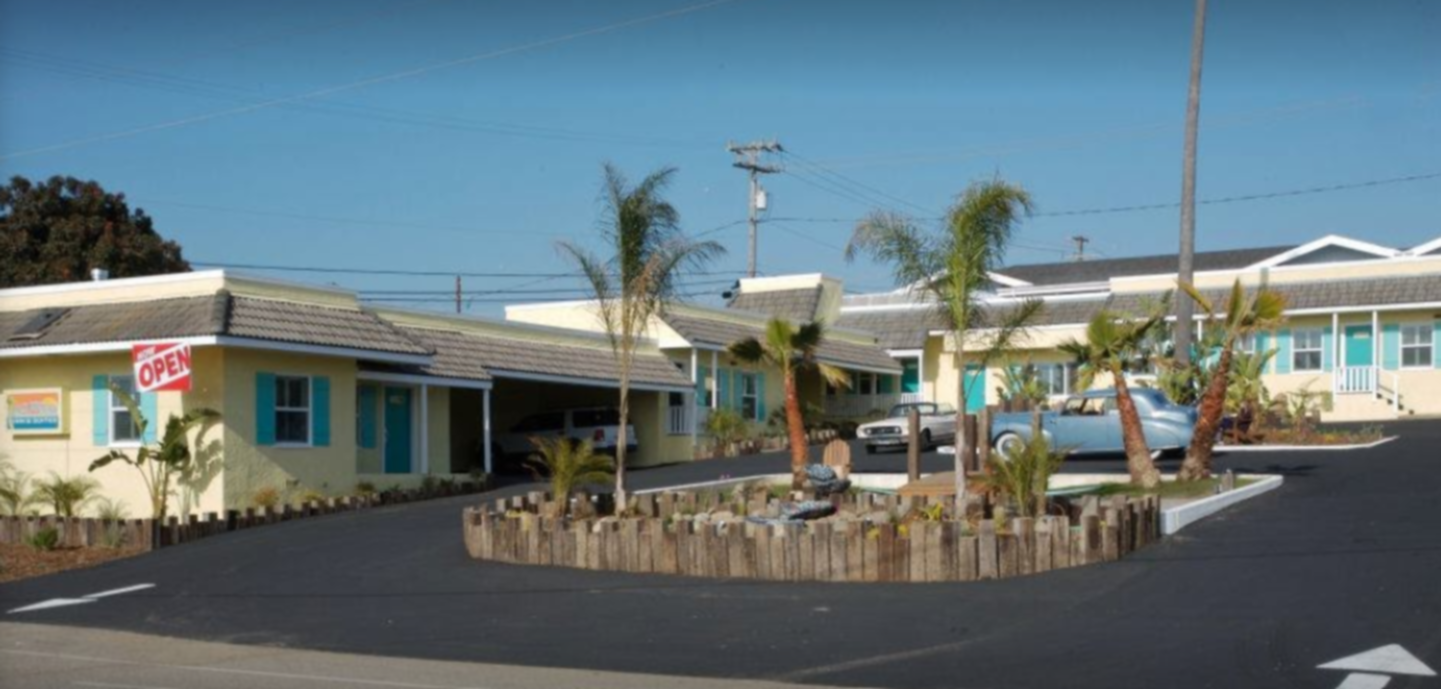 A building that has a sign on the side of a road at Beach Bungalow Inn and Suites.