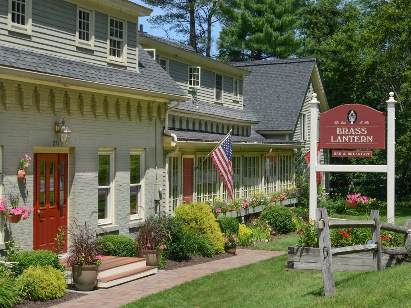 A close up of a flower garden in front of a house at Brass Lantern Inn - Stowe Vermont.
