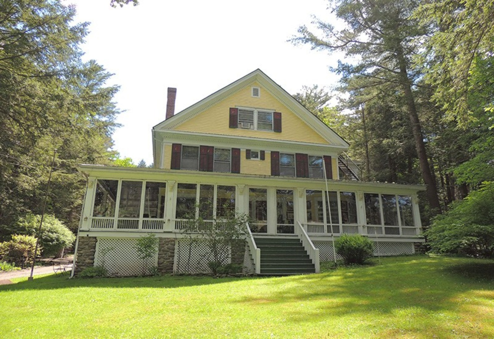 A large lawn in front of a house at Brookview Manor Inn.