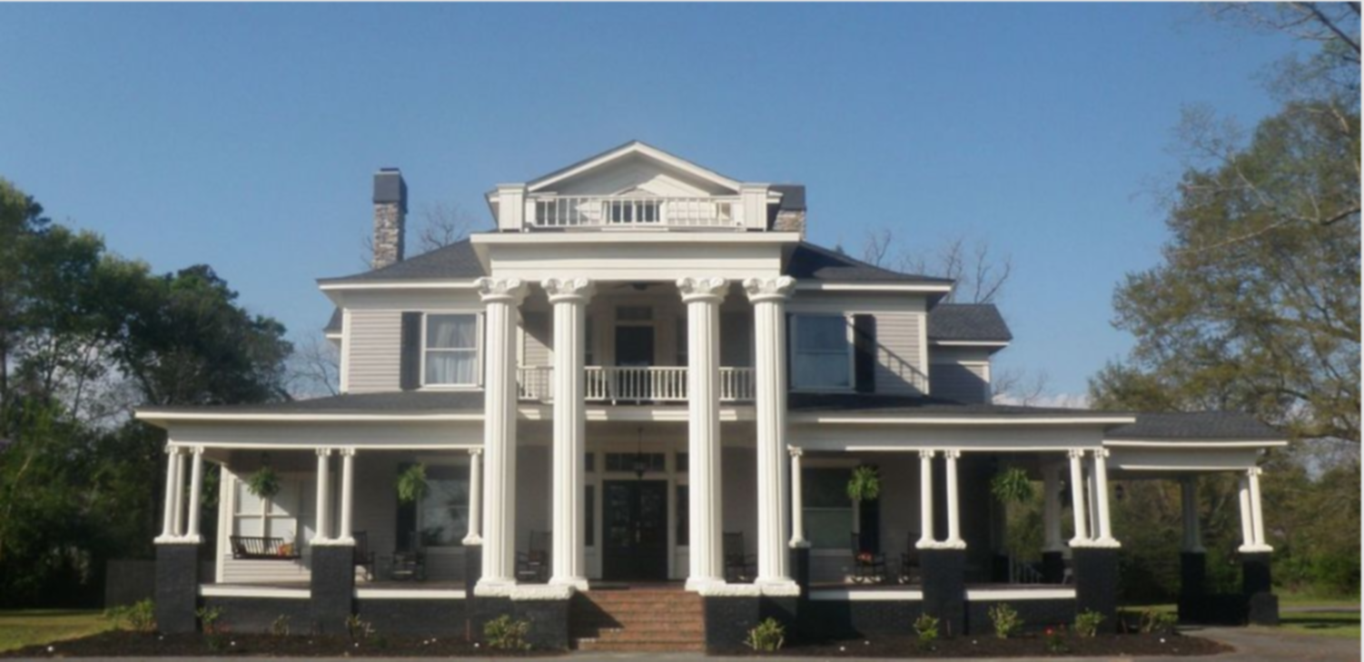 A large white building at Butterfly Mansion Bed & Breakfast.