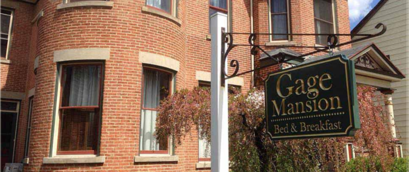 A sign in front of a brick building at Gage Mansion Bed and Breakfast.