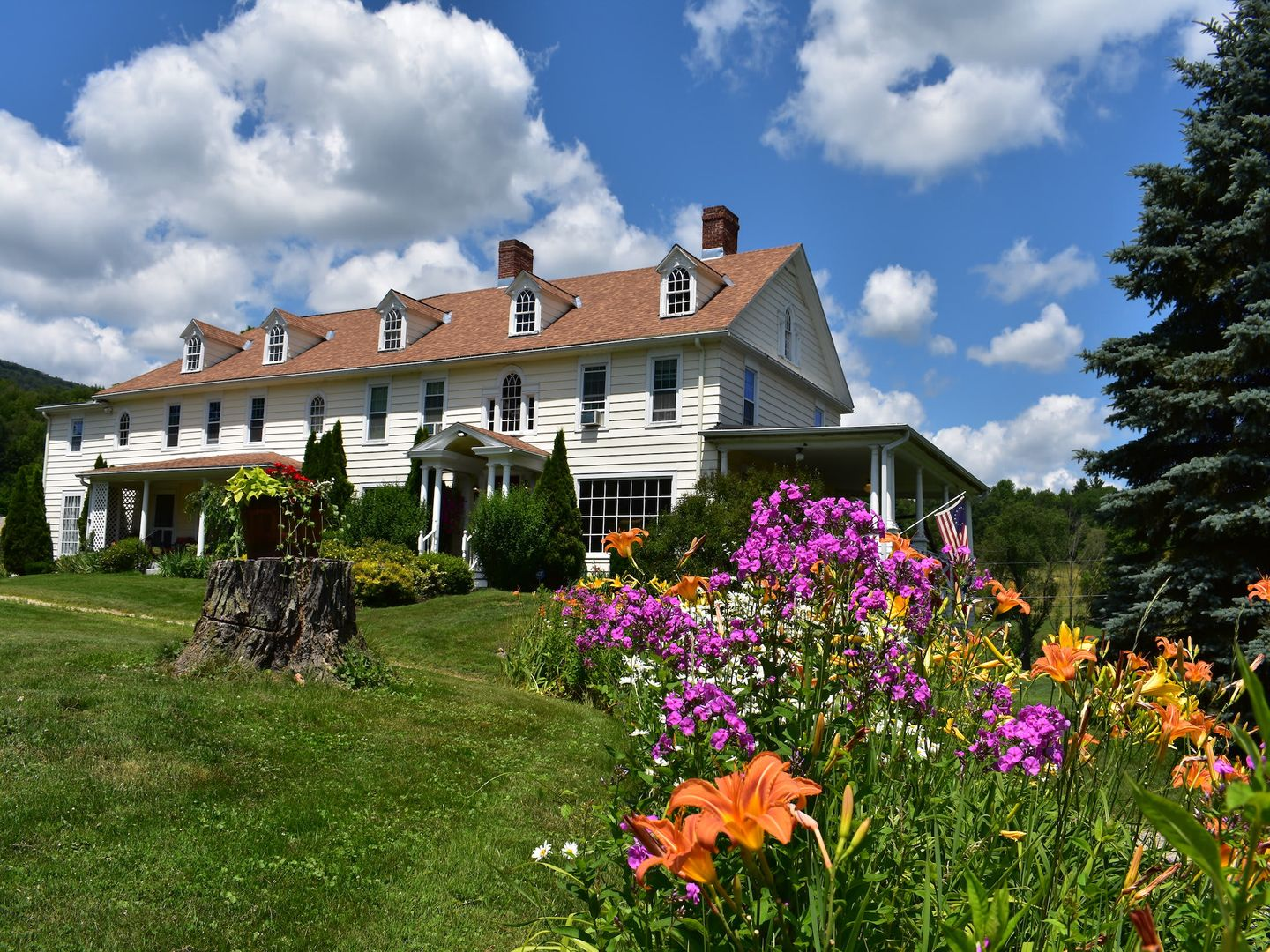 A close up of a flower garden in front of a house at Harbour House Inn B&B.