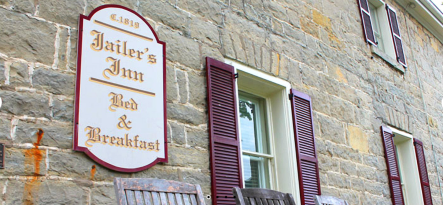 A sign in front of a brick building at Jailer's Inn.