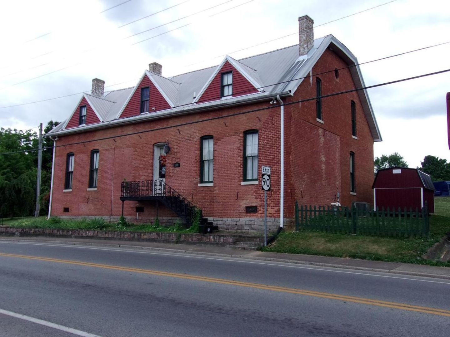 A large red brick building with a clock on the side of a road with surratt house museum in the background at Main Street - Glasgow Kentucky.