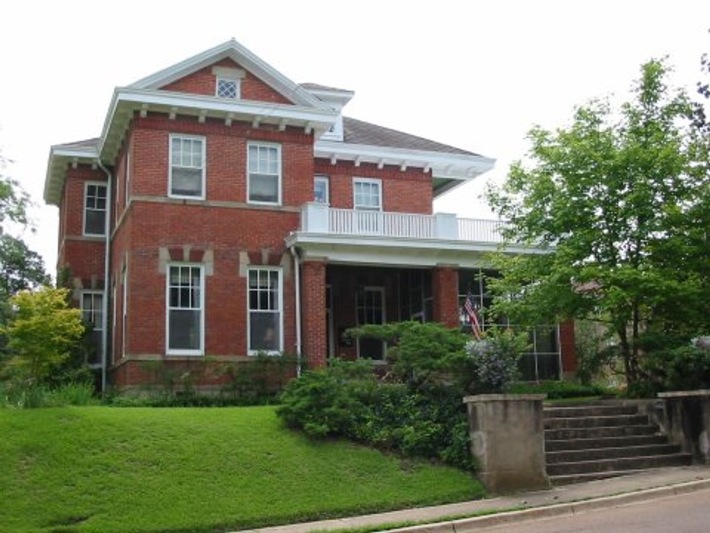 A large brick building with grass in front of a house at Maple Terrace Inn.