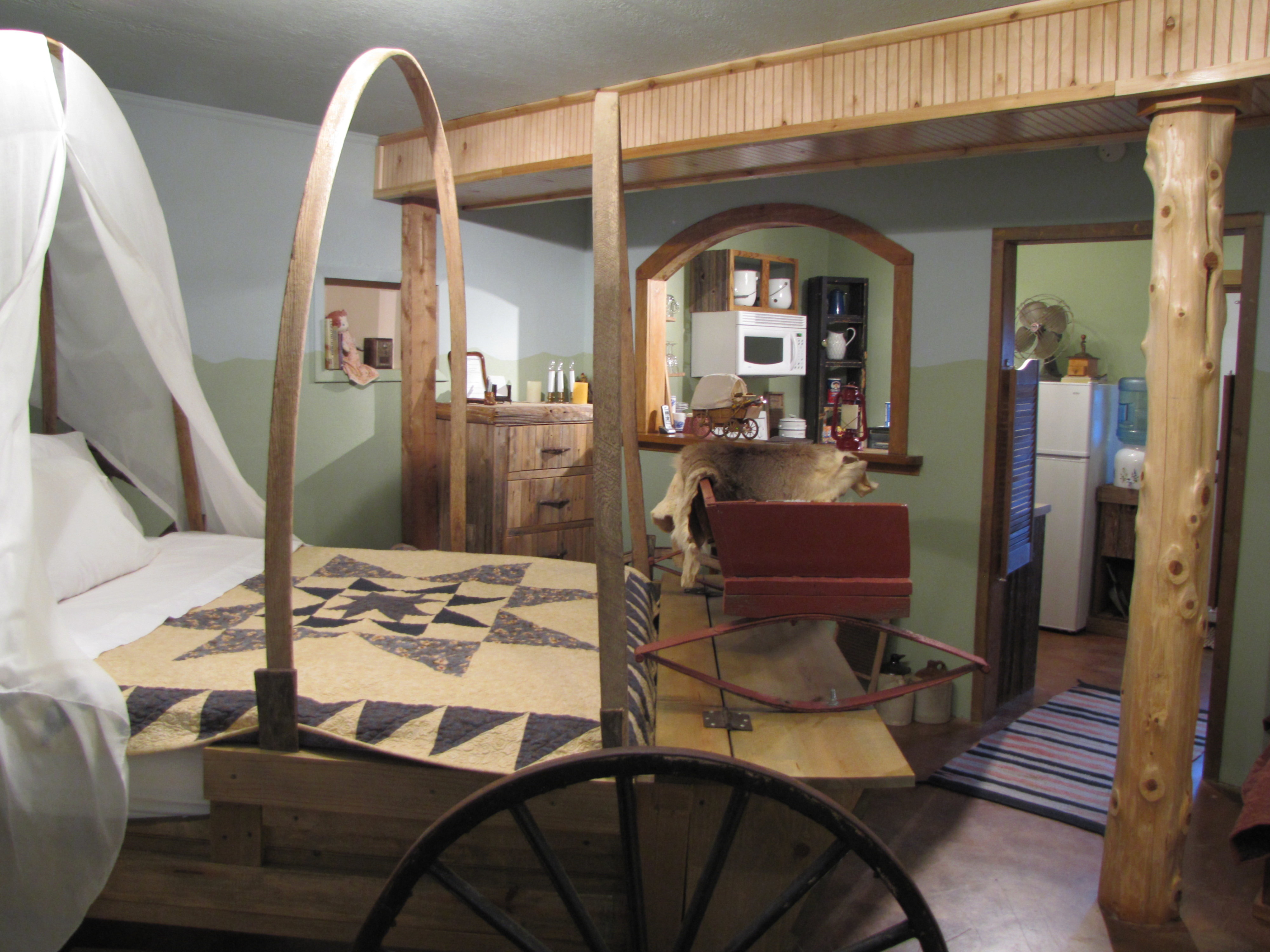 A bedroom with a bed and a chair in a room at Covered Wagon Guesthouse/B&B.
