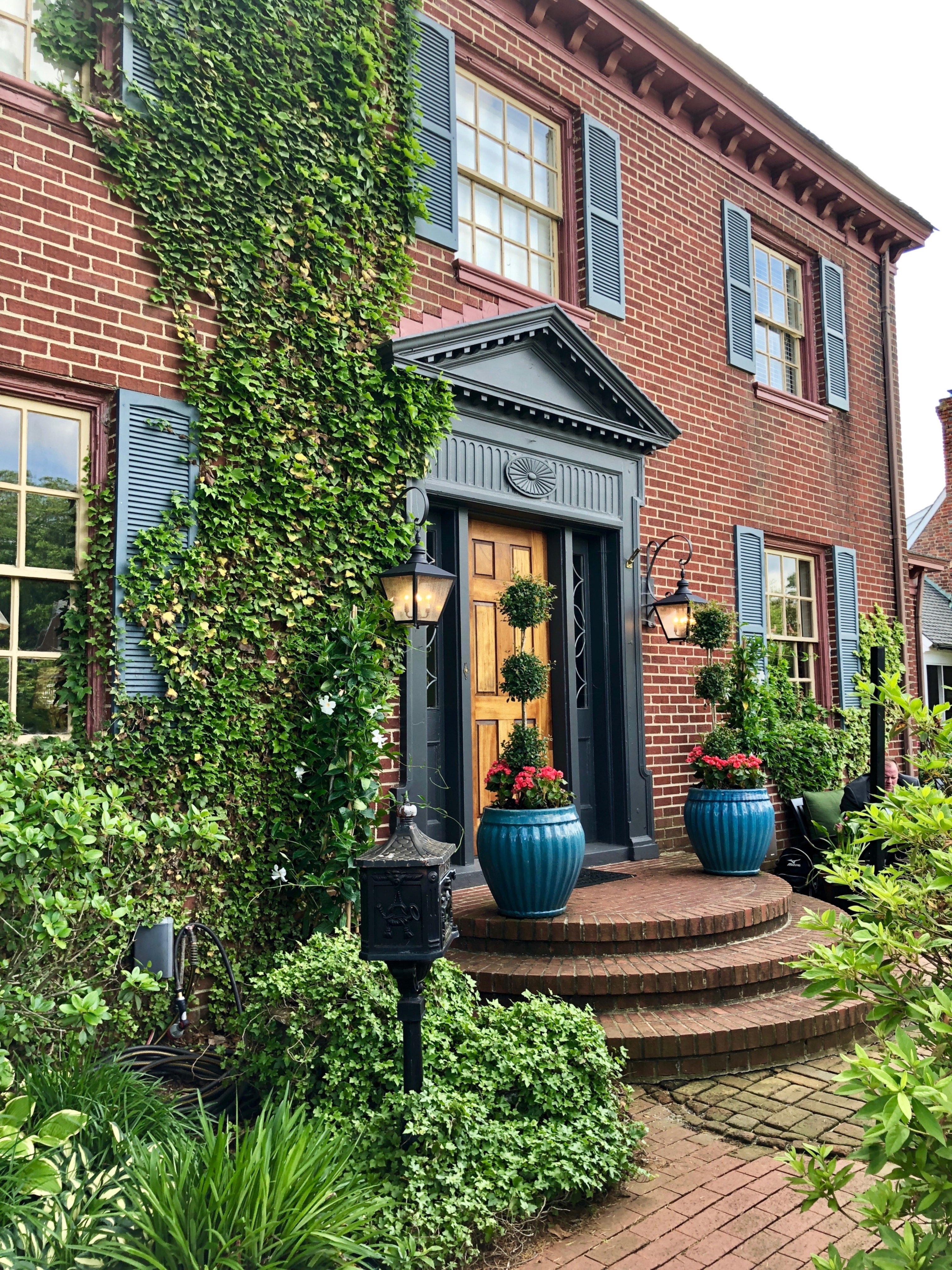 A close up of a flower garden in front of a brick building at Williamsburg Manor Bed & Breakfast.