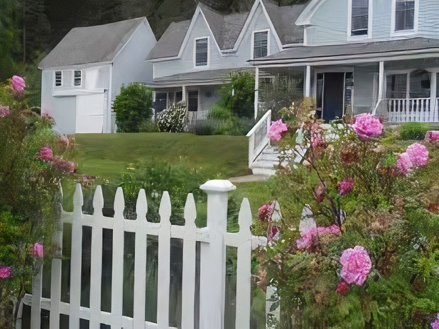 A pink flower is standing in front of a building at Elsa's Inn on the Harbor.