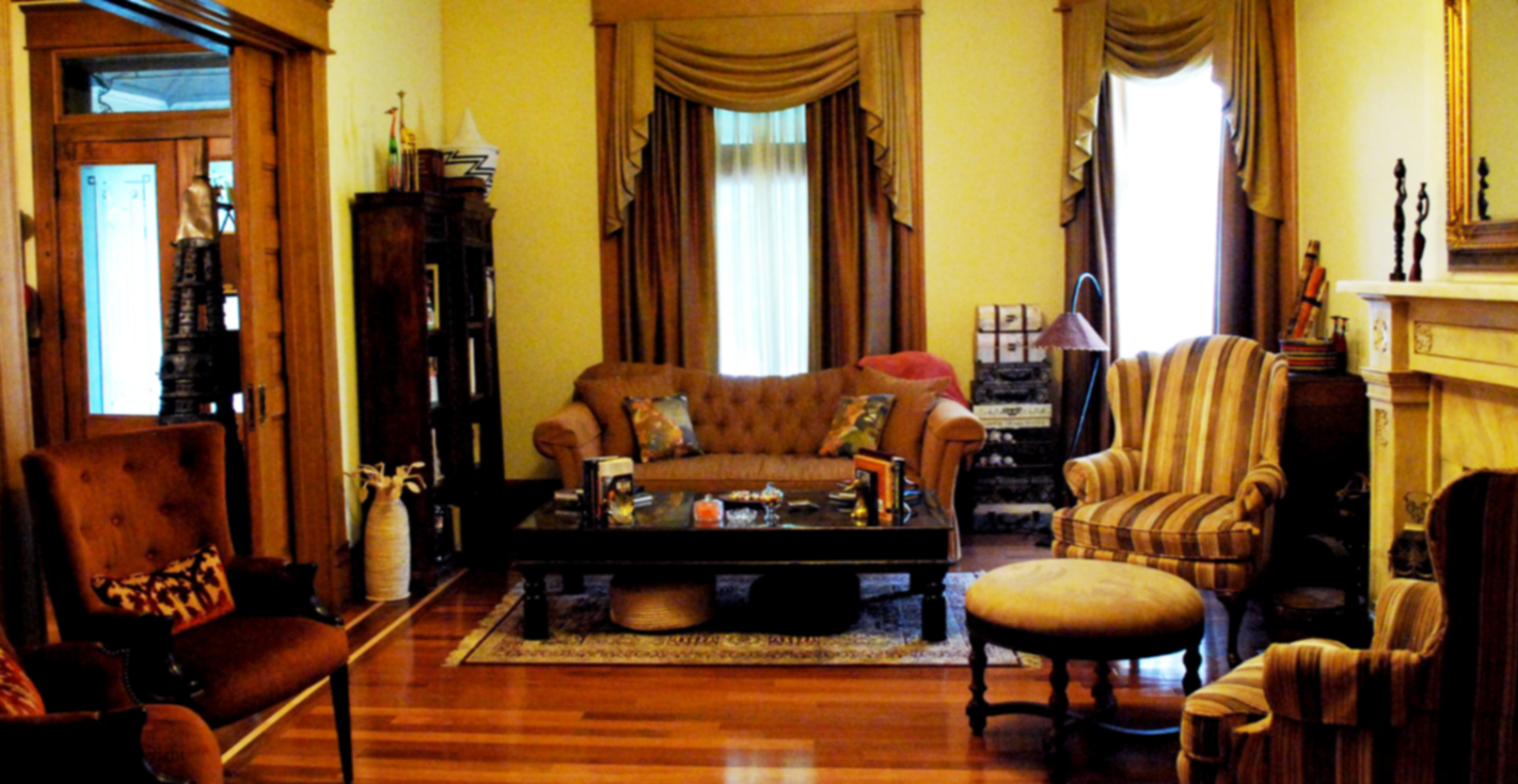 A living room filled with furniture and a fireplace at Old Louisville Fleur de Lis.