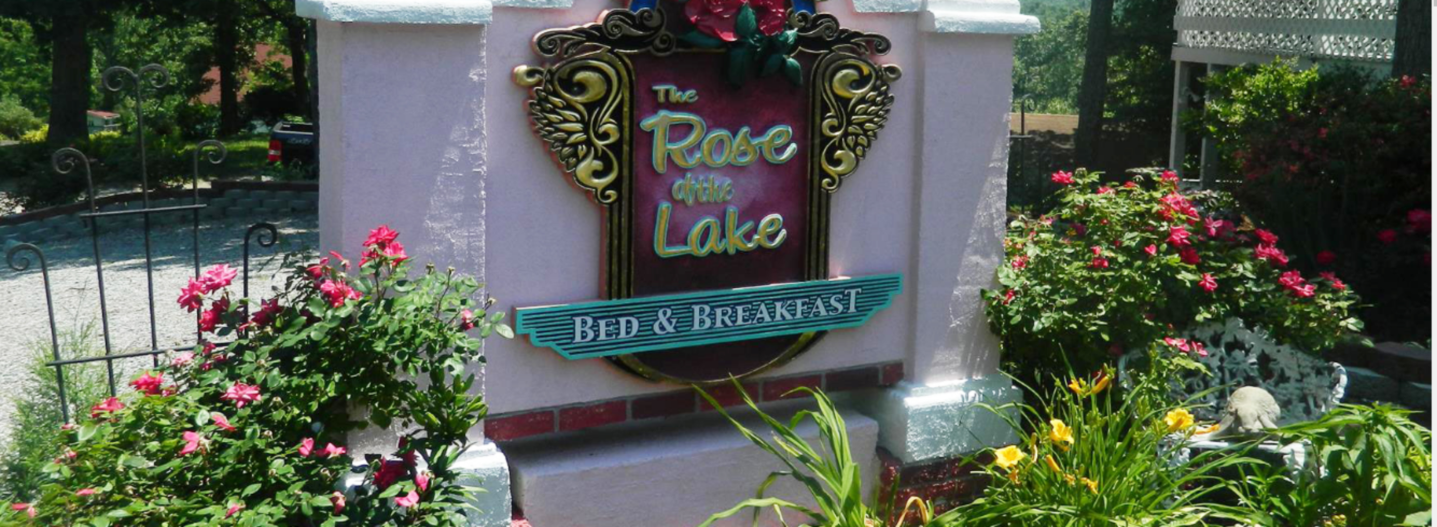 A close up of a flower garden in front of a building at  Rose of the Lake.