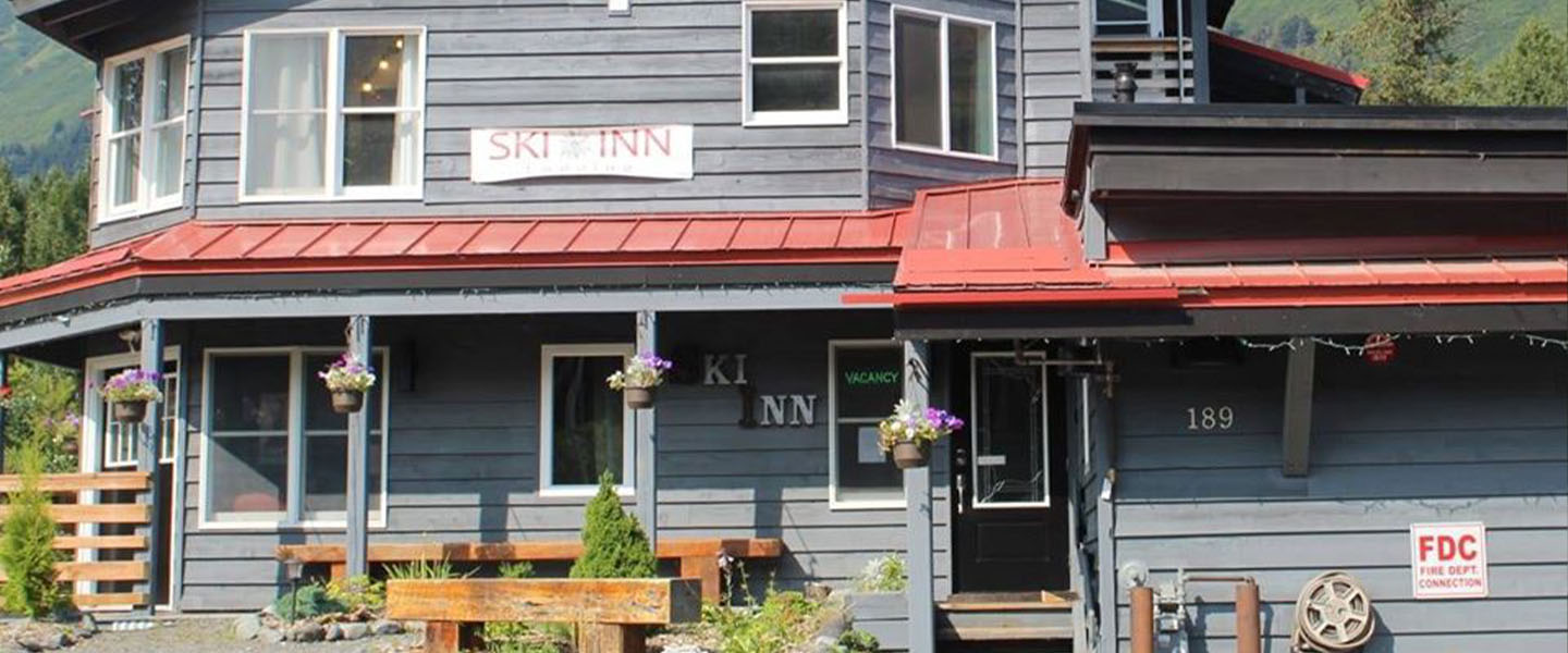 A person standing in front of a building at Ski Inn.