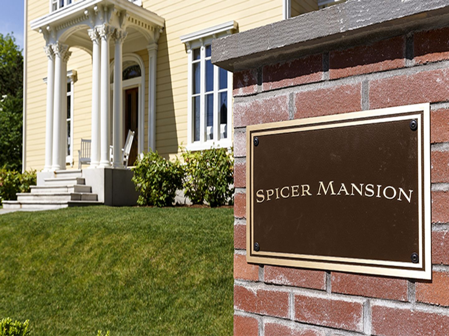 A sign on the side of a building at Spicer Mansion.