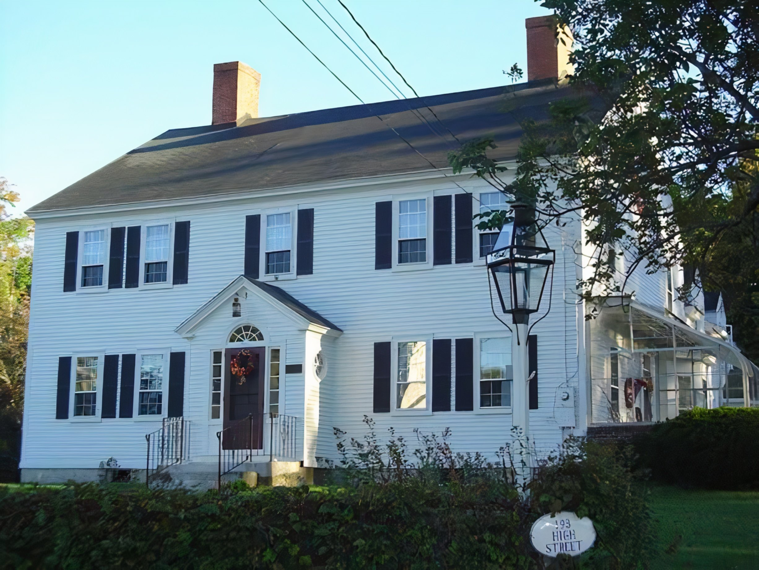 A large white building in front of a house at Stephen Clay Homestead Bed and Breakfast.