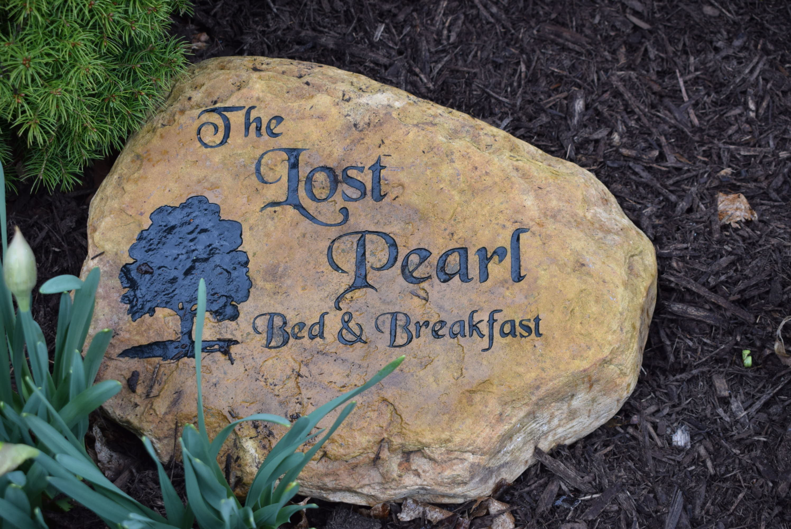 A close up of a sign at The Lost Pearl Bed and Breakfast.