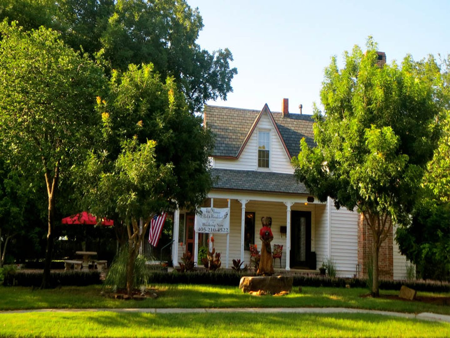 A tree in front of a house at The Manor Bed and Breakfast.